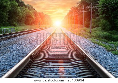 Straight Railroad Into Orange Sunset With Clouds In Sky