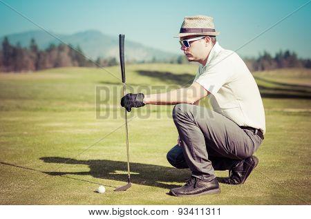 Golfer looking golf shot with club