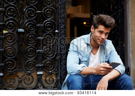 Portrait of handsome young man sending a text message while sitting on the stairs