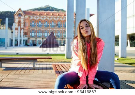 Portrait of a young girl student sitting on a bench near the University resting after training