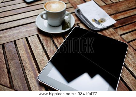 Mock up digital tablet with black touch screen computer bill check with money and cup of coffee