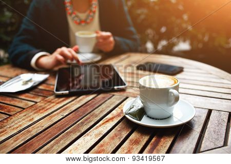 Young business lady sitting on a wooden table in a cafe on which stands its tablet and mobile phone