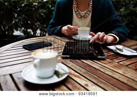 Cup of coffee on the foreground with elegant woman using busy digital tablet at wooden table