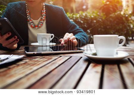 Portrait of a young business lady sitting in cafe working on a tablet and typing messages on phone