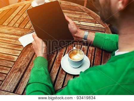Man sitting at the table with cup of coffee while using touch screen tablet with blank screen tablet
