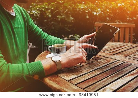 Side view male freelancer sitting on the terrace with cup of coffee and touch screen tablet