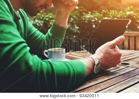 Hands holding digital tablet sitting at wooden table on the terrace of cafe