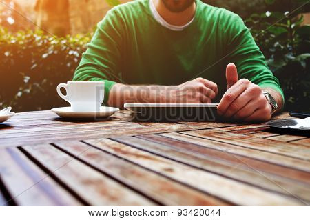 Young man sitting at the table with cup of coffee digital tablet and smart phone