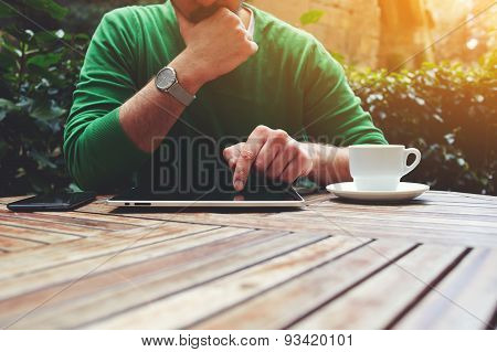 Cropped image of a man sitting in a cafe and working on a tablet tex typing on the touch screen