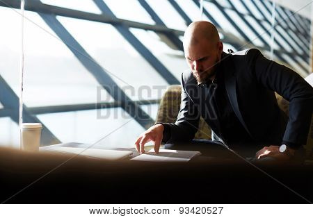 Portrait of a young successful businessman in expensive clothes working with documents in office