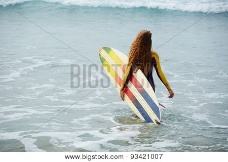 Rear view shot young woman in wetsuit going into the ocean water ready for surf