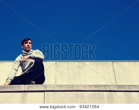 Portrait of a stylish young athlete sitting on the roof and walls on the background of the sky