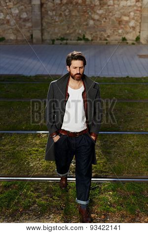 Young stylish hipster with black hair and a beard on a walk in the cool summer evening
