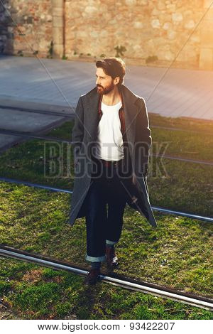 Portrait of an elegant young man dressed a stylish coat that lonely walking the city streets