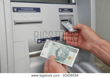 Close up of hand of a man using banking machine in Poland taking sto zlotych