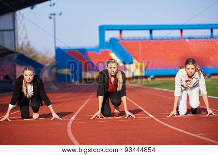 business woman in start position ready to run and sprint on athletics racing track