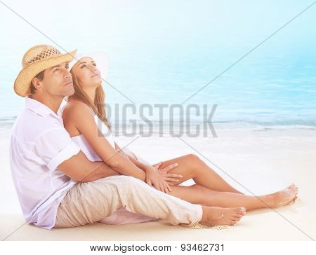 Happy lovers on the beach, beautiful young couple sitting on sandy coast and hugging, dreamy looking up in the sky and enjoying romantic honeymoon  poster