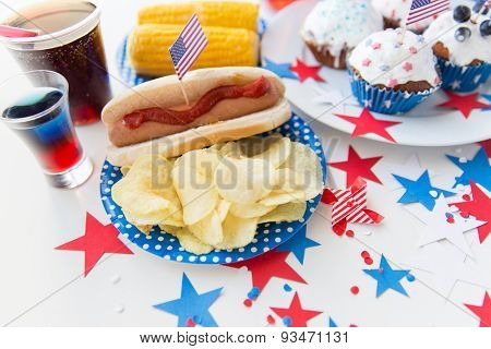 national holidays, celebration, food and patriotism concept - close up of hot dog with american flag decoration, potato chips and drinks on 4th july at party on independence day poster