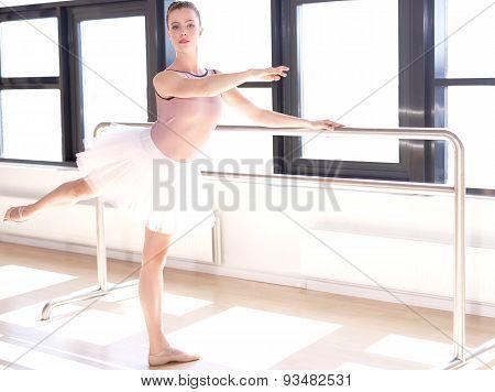 Ballerina Doing Barre Exercises In Sunny Studio