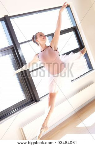 Young Ballerina Leaping Through Air In Studio