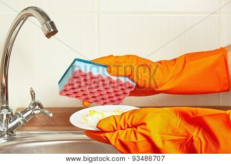 Hands in rubber gloves with dirty plate over the sink in kitchen