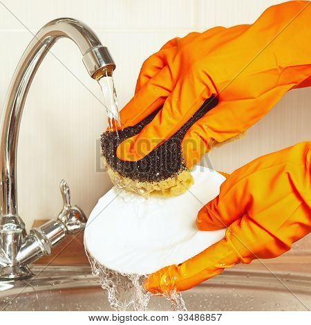 Hands in rubber gloves with sponge wash dishes under running water