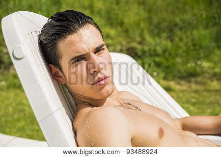 Shirtless Young Man Sunbathing in Lounge Chair on Grass
