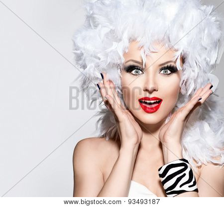 Funny Surprised Woman in white feather wig, holiday make up and accessories. Fashion Model Girl portrait. Creative Makeup and manicure.  Heathers on a head. Hairstyle.