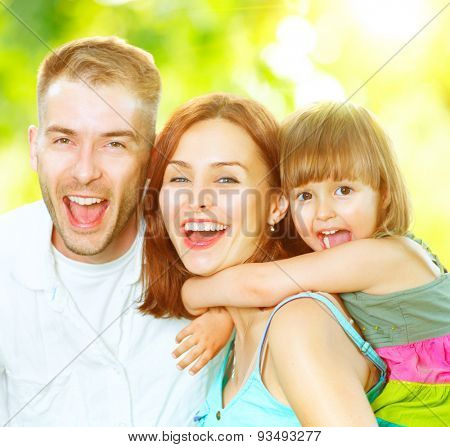 Happy joyful young family father, mother and little son having fun outdoors, playing together in summer park, countryside. Mom, Dad and kid laughing and hugging, enjoying nature outside. Sunny day