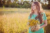 Artistic portrait of young gorgeous brunette on green meadow. Shallow depth of field poster
