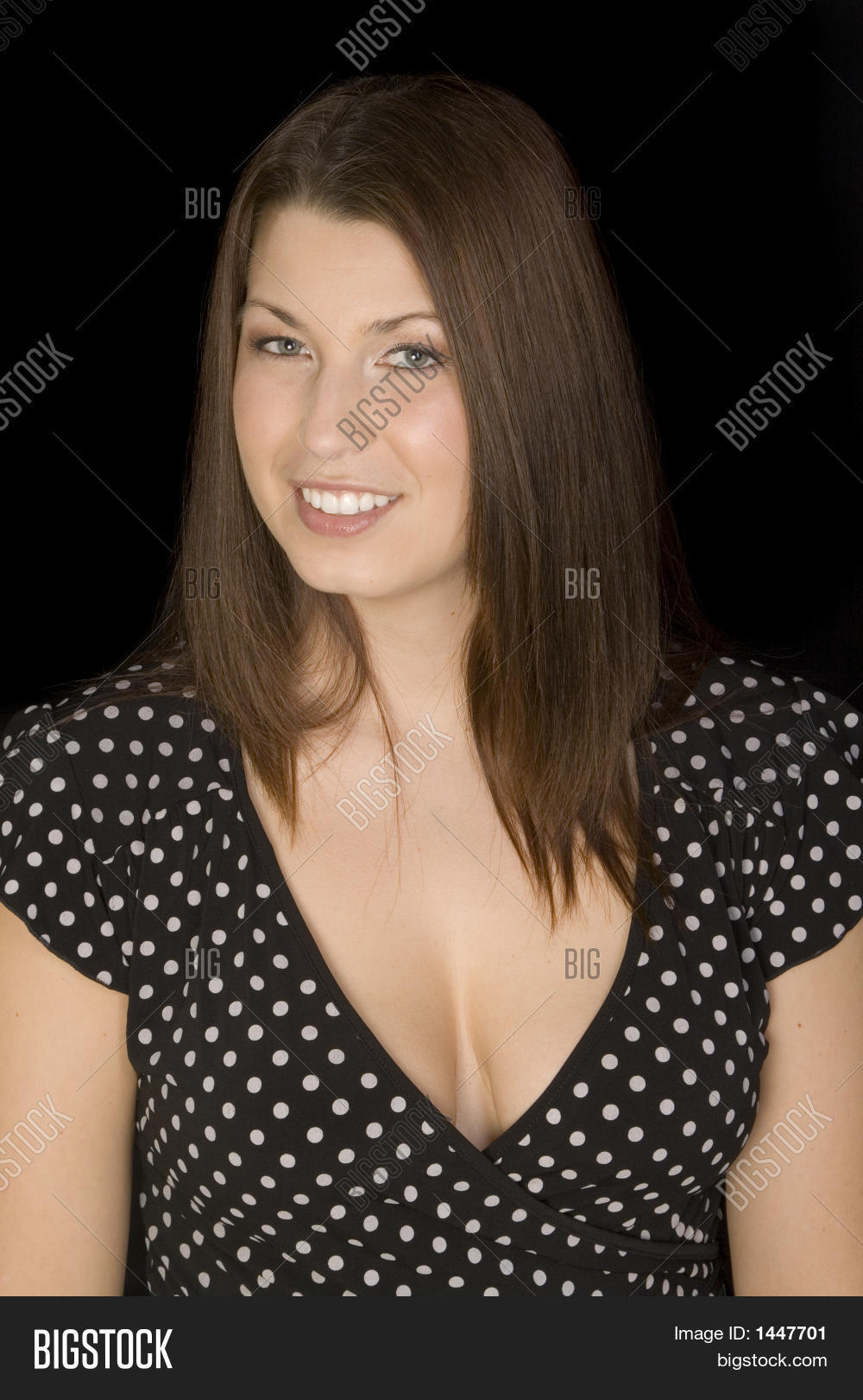 woman in black dress smiling busty with cleavage on black background