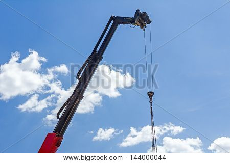 Telescopic mobile crane has high elevated chains for lifting hook against blue sky.