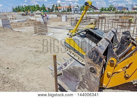 Excavator is moving over building site with raised up front bucket vibration plate compactor machine transport.