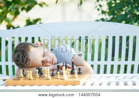 child sleeps on a chessboard. tired boy fell asleep at the table during a game of chess. the concept of educational overload in children