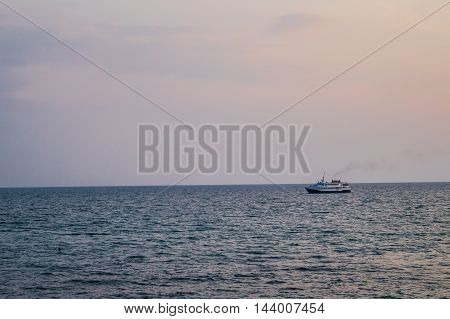The ship sails the sea in the evening