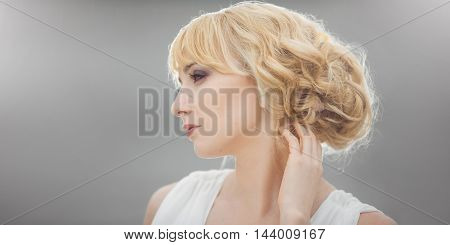 Portrait of a young beautiful bride looking down gently touching her hair outdoors on gray background. Professional make-up and hair-style. Side view. Stretched gray background with copy space