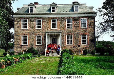 New York City - July 29 2014: Visiting school children at the south front doorway of Georgian 1748 Van Cortlandt Manor house built in dressed fieldstone with a double-hipped roof