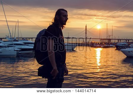 guy with long hair in silhouette standing on the beach with a camera where yachts are docked at the pier at sunset in summer, in the distance, the cable-stayed bridge