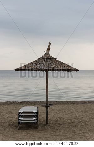 Reed Parasol With Sun Loungers on Sandy Beach. Umbrella and Sunbeds on Gloomy Weather and Calm Sea. Reed Umbrella and Easy Chairs on a Background of Cloudy Sky.