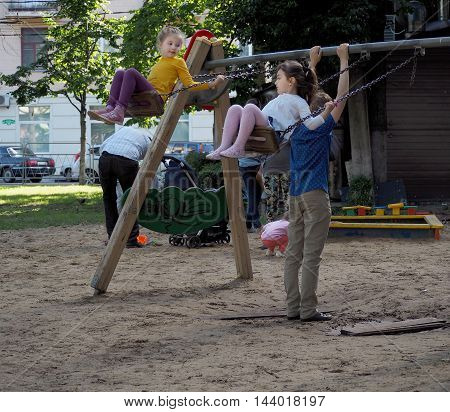 VORONEZH, RUSSIA - June 12, 2016: Two elementary age girls on a swing. Both look at each other. On the playground in a city park. June 12, 2016 in Voronezh, Russia