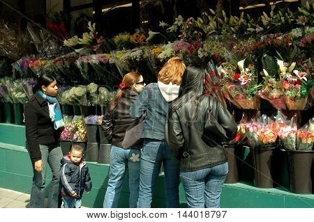 New York City - March 31 2005: Women shopping for flowers at an upper west side market on Broadway