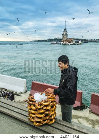 Istanbul Turkey - December 04 2013: Maidens Tower in Istanbul Turkish bagel salesman. European part of Istanbul in the background against the shore. Left Blue Mosque medium Hagia Sophia Topkapi palace dome seem right. The Maiden's Tower (Turkish: Kiz Kule