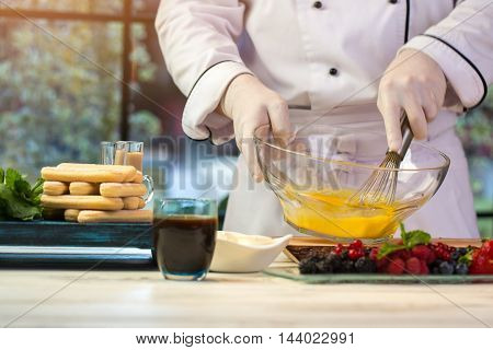 Hand whisks egg in bowl. Biscuits and glass with drink. How to make tiramisu. Pastry chef is busy.