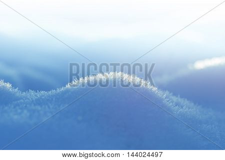 closeup of crystal snowfield soft color gradient blue and white winter background with copy space