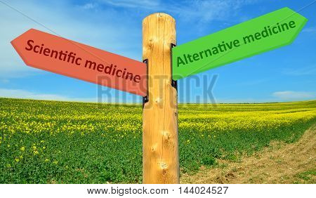A direction sign with opposite arrows with inscription scientific medicine and Alternative Medicine