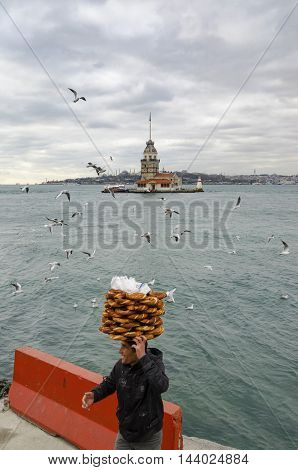 Istanbul Turkey - December 04 2013: Maiden Tower. A young salesman (Simit) bread vendor. European part of Istanbul in the background against the shore. Left Blue Mosque medium Hagia Sophia Topkapi palace dome seem right. The Maiden's Tower (Turkish: Kiz K