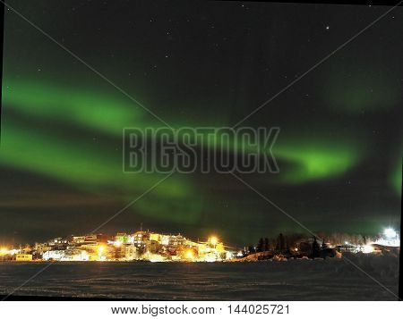 Green Northern Lights Over Village in the Snow