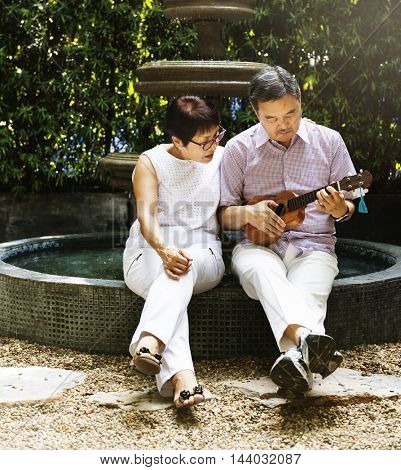 Senior Couple Fountain Ukulele Instrument Concept