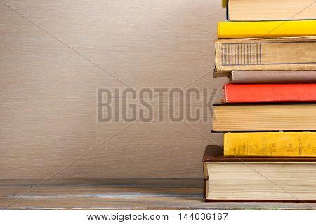 Colorful composition with vintage old hardback books, diary on wooden deck table and beige background. Books stacking. Back to school. Copy Space. Education background