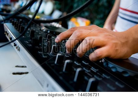 Close-up image of mixing console and DJ's hands during his job at party